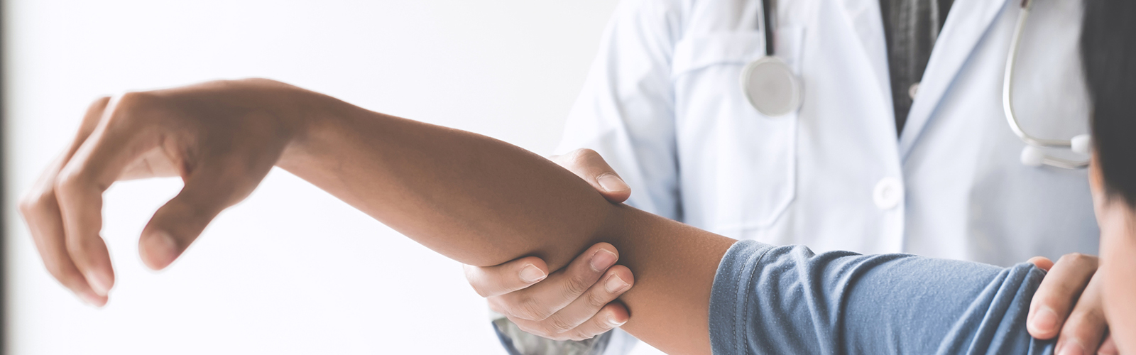 Doctor checking patient's elbow