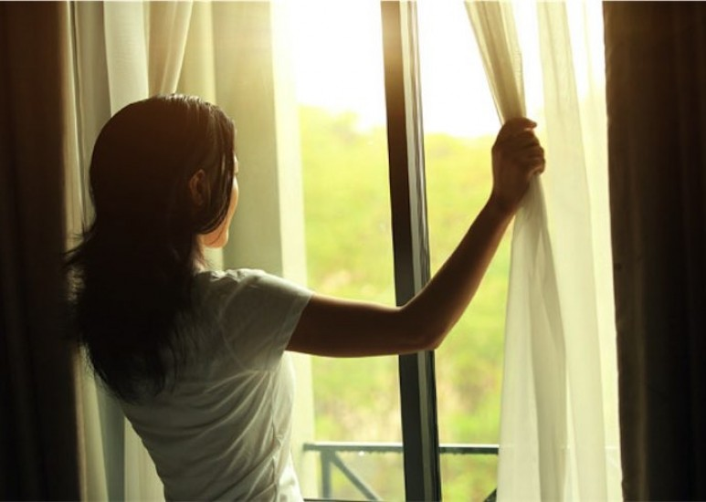 Woman pulling back curtains to look at sunrise