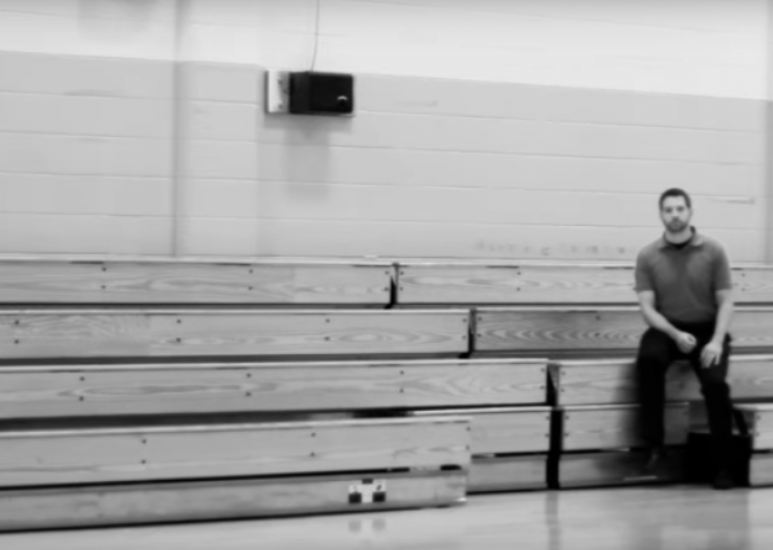 Teacher sitting in the bleachers of a gym