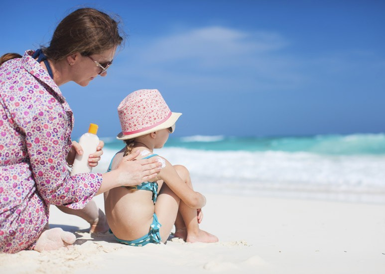 Mom applying sunscreen to child at beach