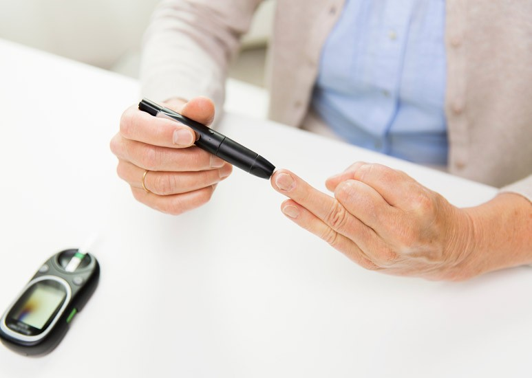 Senior checking diabetes blood sugar