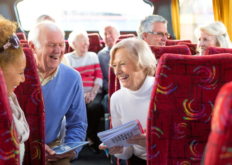 Seniors traveling on bus, doing crossword