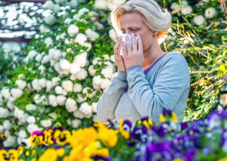 Woman sneezing from spring allergies