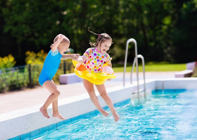 Kids jumping into a swimming pool