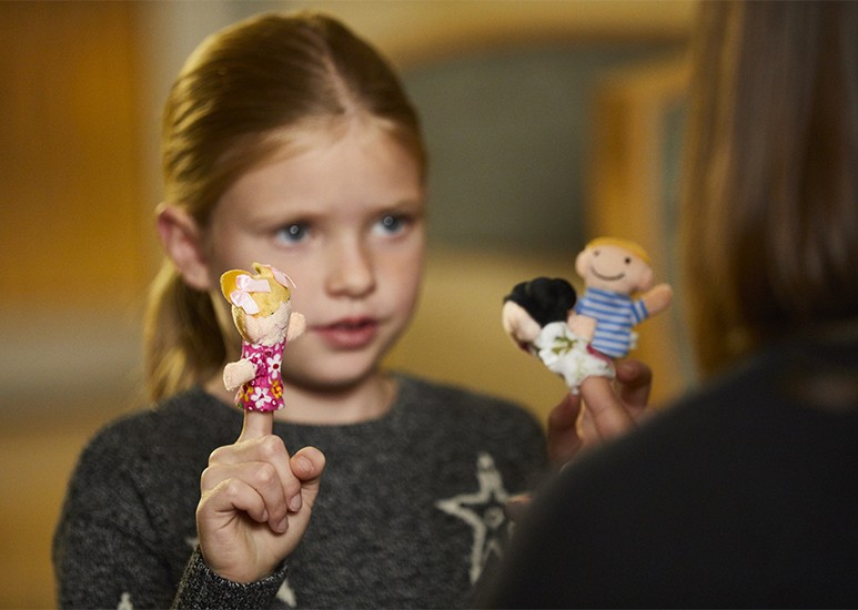 Child and therapist doing play therapy with finger puppets