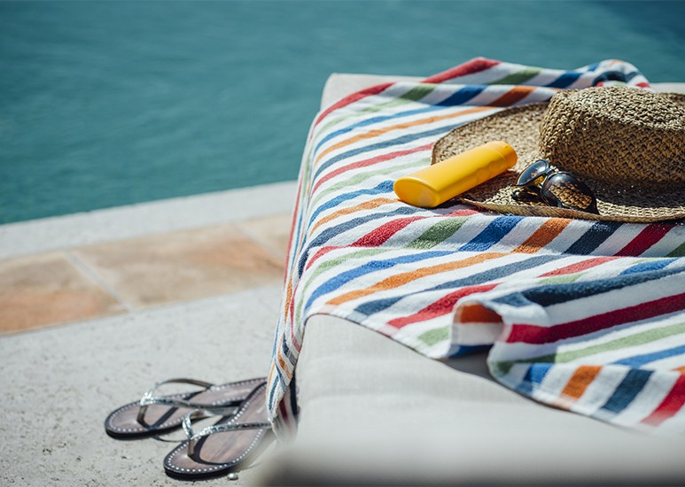 Lounge chair with towel and sunblock by pool