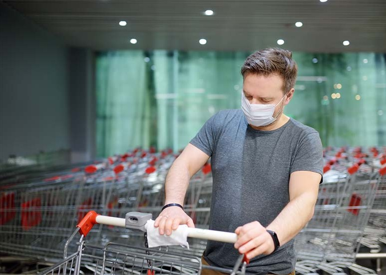 man wearing face mask using a disinfecting wipe to clean shopping cart