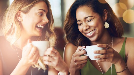 Two female friends laughing over coffee
