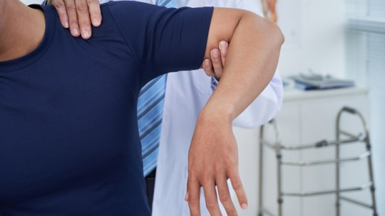 Physician checking shoulder injury