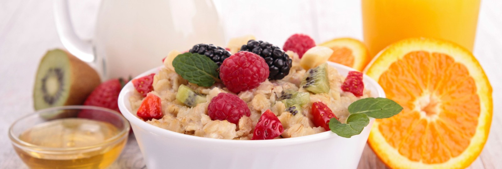 Healthy breakfast foods - fruit, orange juice, oatmeal and milk