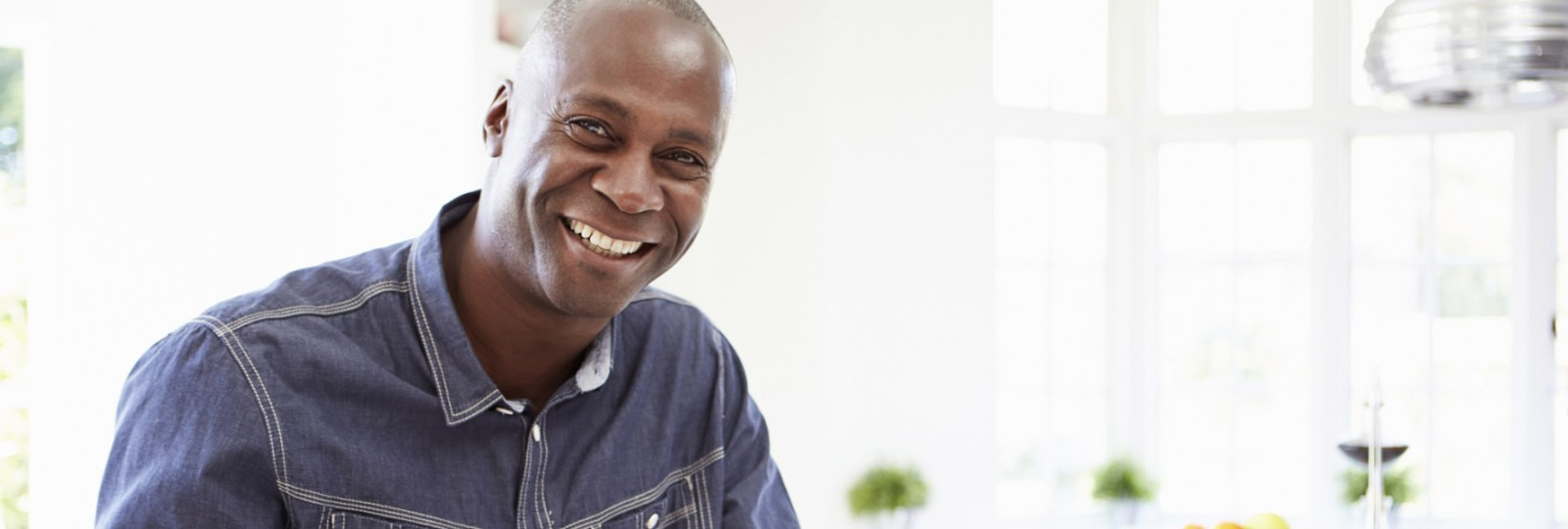 African American man in his 40s smiling in home kitchen