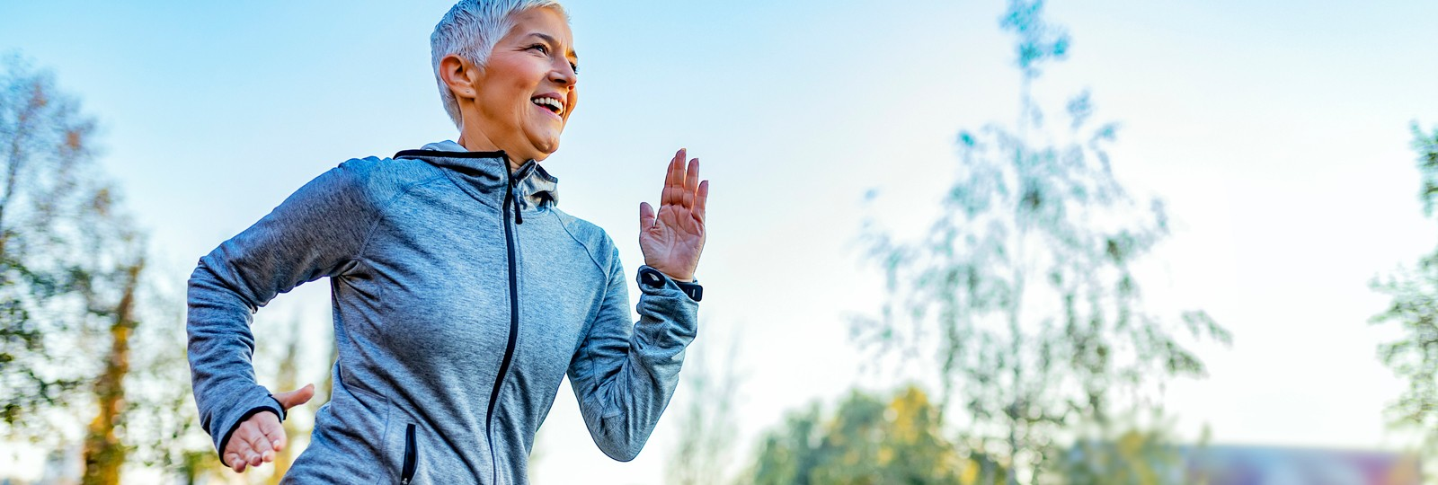 Happy older woman jogging outside