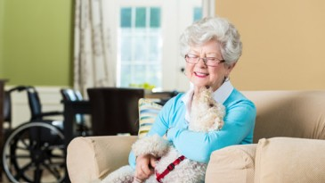 Elderly woman enjoying time at home with her puppy