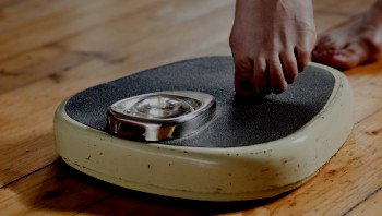 Woman placing her toe on a weight scale